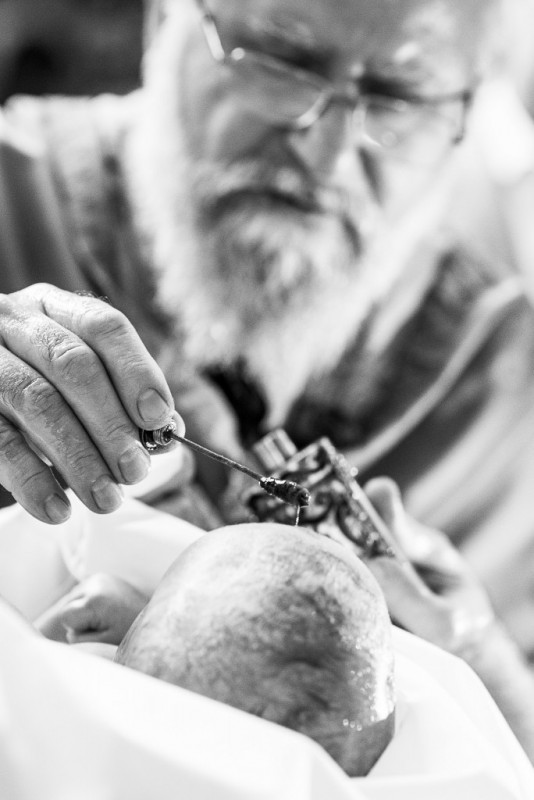 Prister tröpfelt Öl auf das getaufte Kind in der griechisch orthodoxen Kirche in Stuttgart-Feuerbach
