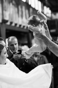Taufe Fotograf Baby wird aus dem Taufbecken gehoben in der griechisch orthodoxen Kirche in Stuttgart